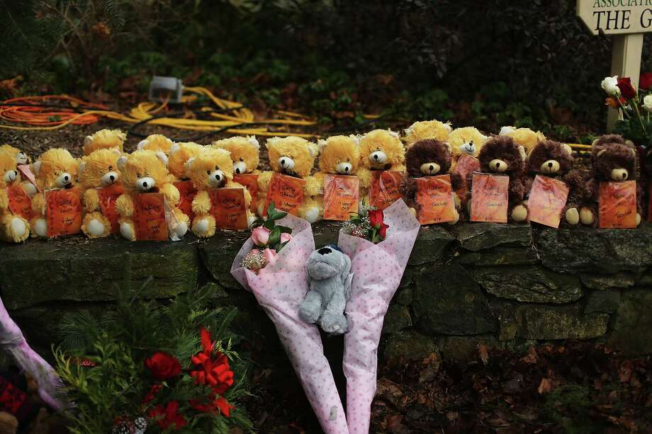 Twenty-six teddy bears --- one representing each victim at Sandy Hook Elementary School --- and flowers form a memorial just down the street from the school in Newtown. Photo: Spencer Platt, Getty Images / Getty Images