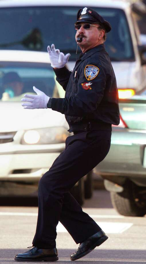 In this Dec. 13, 2012 photo, former Providence Police Department office Tony Lepore directs traffic at an intersection on Dorrance Street in Providence, R.I. Lepore is know as the dancing cop because of his energetic and rhythmic style of moving vehicles and pedestrians through an intersection. Photo: Stephan Savoia, AP / AP