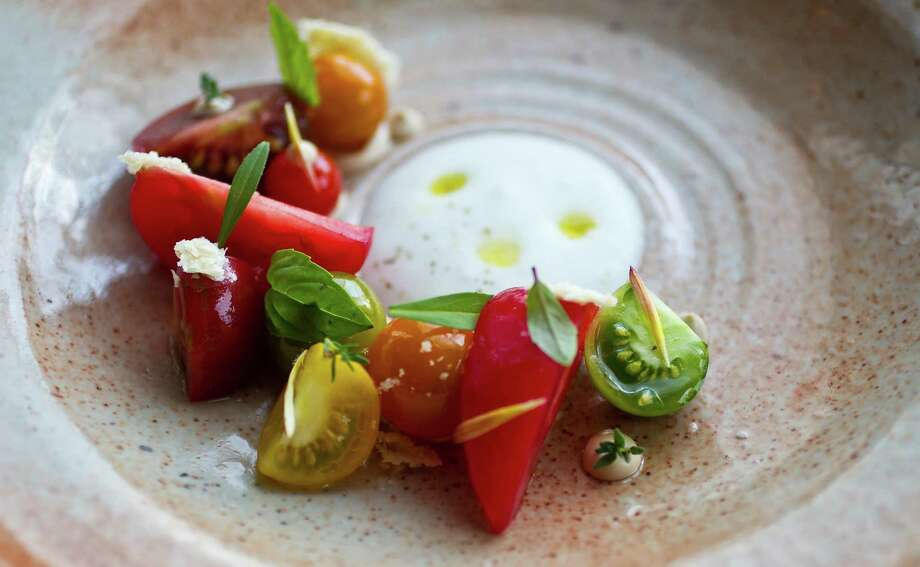 Tomatoes (from Three Sisters Farm) served with bay leaf, pine nut puree, spring herbs with milk foam at Oxheart. Photo: Karen Warren, Staff / 2012  Houston Chronicle