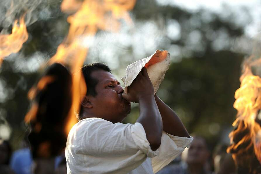A Mayan shaman blows a conch during a ceremony for the coming of the end of the Mayan cycle.