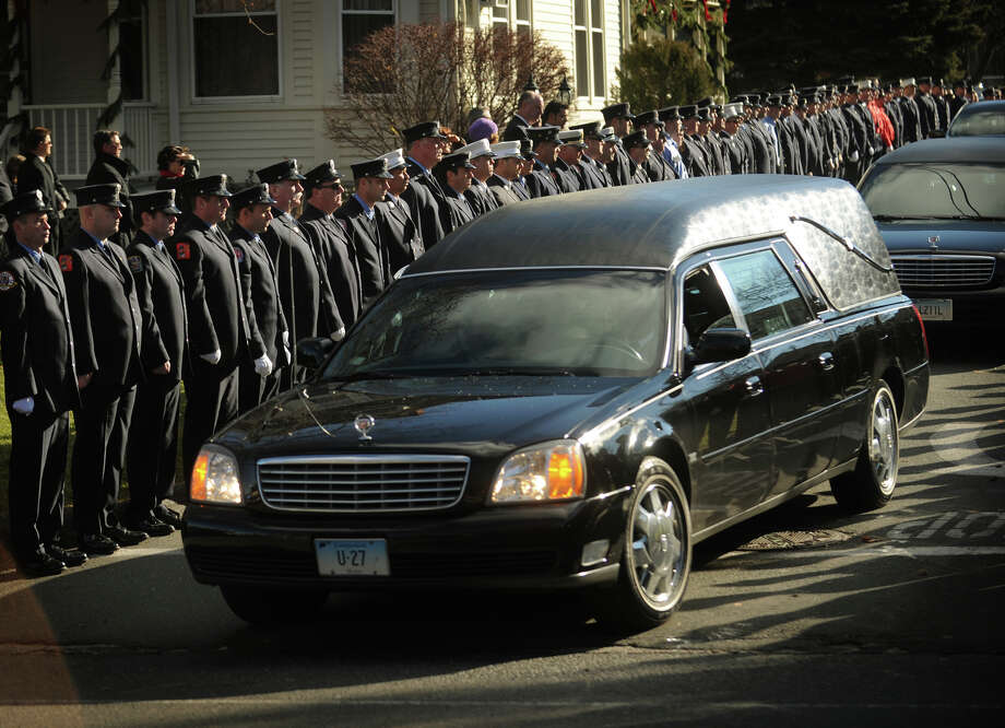 A hearse containing the casket of Daniel Barden, one of the twenty children killed in the Sandy Hook Elementary School shooting, exits as a line of firefighters stand at attention outside St. Rose of Lima Catholic Church in Newtown on Wednesday, December 19, 2012. Photo: Brian A. Pounds / Connecticut Post