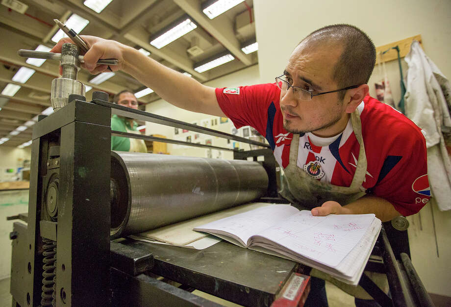Juan de Dios Mora adjusts the pressure of a printing press at UTSA, where he is a printmaking lecturer.  Photo: Michael Miller, For The Express-News / San Antonio Express-News