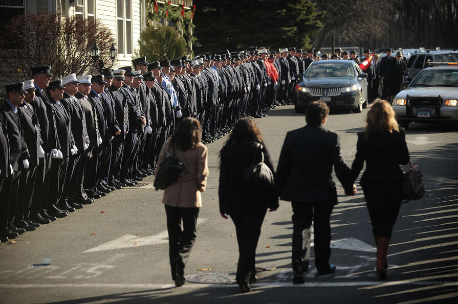 Mourners enter past lines of firefighters outside the funeral for Daniel Barden, one of the twenty c