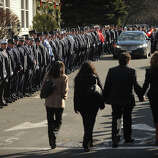 Mourners enter past lines of firefighters outside the funeral for Daniel Barden, one of the twenty children killed in the Sandy Hook Elementary School shooting, at St. Rose of Lima Catholic Church in Newtown on Wednesday, December 19, 2012.