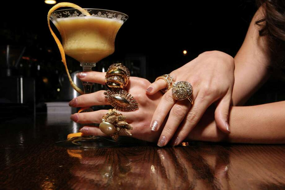 Ben & Jerry's  Hand holding the cocktail, top to bottom: Alexis Bittar gold-sculpted and crystal-adorned ring ($135, Saks Fifth Avenue); art-deco stretch-band ring by Jessica Simpson ($30, Dillard's North Star Mall); pearl surrounded by adorned leaves ring by Miriam Haskell ($250, Julian Gold). Hand on right: middle finger is wearing a crystal-encrusted dome ring by Alexis Bittar ($147, Saks Fifth Avenue); on the pinky finger is a crown ring motif by Ana & Ava ($15, Dillard's at North Star Mall). Photo: Helen L. Montoya, Staff / ©SAN ANTONIO EXPRESS-NEWS