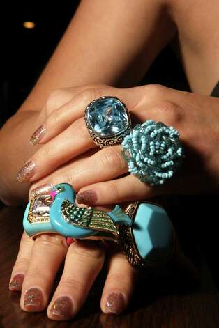 Top hand: On the ring finger is a floral aqua stretch-band ring ($15, Boutique at the Woman's Club of San Antonio); on the middle finger is a blue and silver-plated cubic ziconia cocktail ring by Barse ($78, Dillard's North Star Mall). Bottom hand: On the ring finger is a turquoise- and crystal-encrusted ring ($140, Julian Gold); on the middle finger is a whimsical turquoise- and crystal-adorned bird by Betsey Johnson ($65, Dillard's North Star Mall); on the index finger is a chunky glass ring in turquoise and bronze by Barse ($48, Dillard's North Star Mall). Photo: Helen L. Montoya, Staff / ©SAN ANTONIO EXPRESS-NEWS