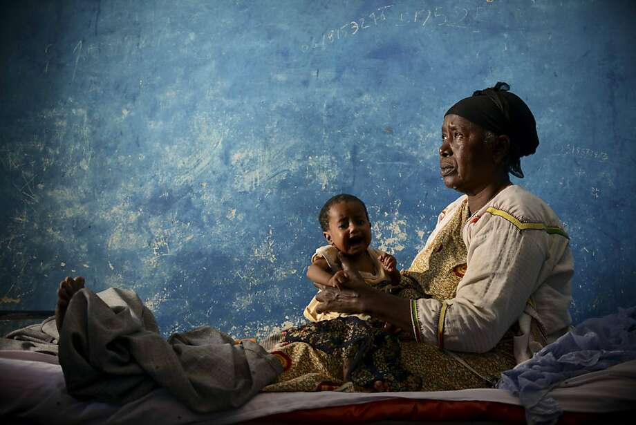 A woman holds an upset child during a visit by Unicef and WHO program personnel in Merka, southern Somalia, where cases of cholera and dengue fever have been reported. Photo: Tobin Jones, AFP/Getty Images