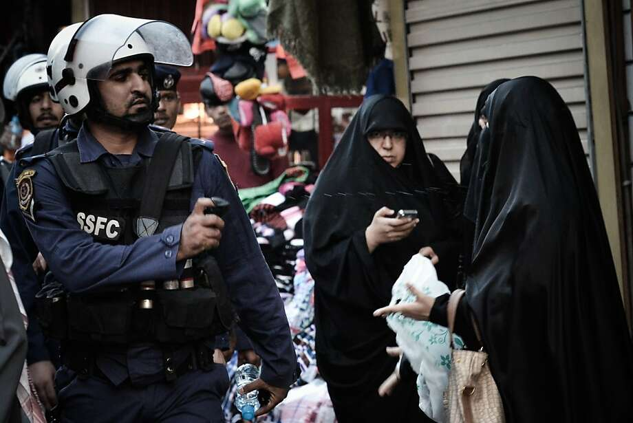 """Another nonchalant pepper-spraying cop:In Manama, Bahrain, a police officer squirts a Shiite Muslim woman with the stinging liquid during an anti-government demonstration. Police also used tear gas and stun grenades to disperse dozens of anti-regime Shiite demonstrators marking the opposition's """"Martyrs' Day."""" Martyrs' Day commemorates the deaths of regime opponents in clashes with security forces in the 1990s. Photo: Mohammed Al-Shaikh, AFP/Getty Images"""