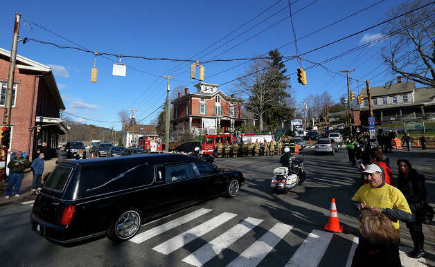 A hearse crosses the main intersection in the Sandy Hook village of Newtown, Conn., during a procession toward St. Rose of Lima parish cemetery before burial services for Daniel Gerard Barden, one of the students killed during the Sandy Hook Elementary shooting, Wednesday, Dec. 19, 2012. The small, quiet town has seen gridlock traffic caused by funeral processions as well as the large number of national and international media covering the aftermath of the shooting. Barden, 7, was killed when the gunman, Adam Lanza, walked into the school, Dec. 14, and opened fire, killing 26 people, including 20 children, before killing himself. Photo: AP