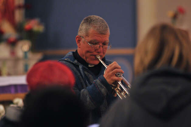 Father James Marshall of Our Lady of Guadalupe Church plays his trumpet during a rehearsal for the church's yearly Posada. Photo: Robin Jerstad/For The Express-Ne