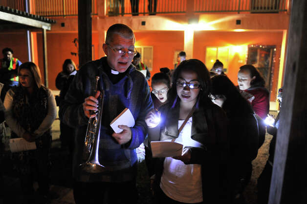 Father James Marshall (left) and Jasmine Marshall (no relation) sing during the Our Lady of Guadalupe Church Posada as it stopped at the San Jacinto Senior Housing Development. Photo: Robin Jerstad/For The Express-Ne