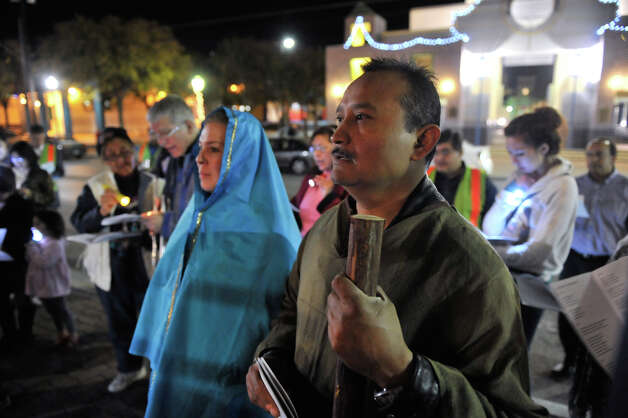 Jose Martinez as Joseph (right) and Marissa Benavidez as Mary lead the year Our Lady of Guadalupe Church Posada along Guadalupe St. Photo: Robin Jerstad/For The Express-Ne