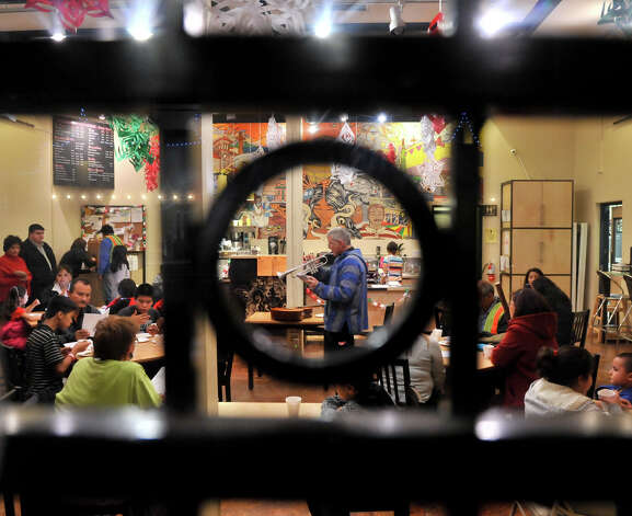 Father James Marshall of Our Lady of Guadalupe Church plays Christmas songs on his trumpet inside Guadalupe Stree Coffee during refreshments at the end of the Posada. Photo: Robin Jerstad/For The Express-Ne