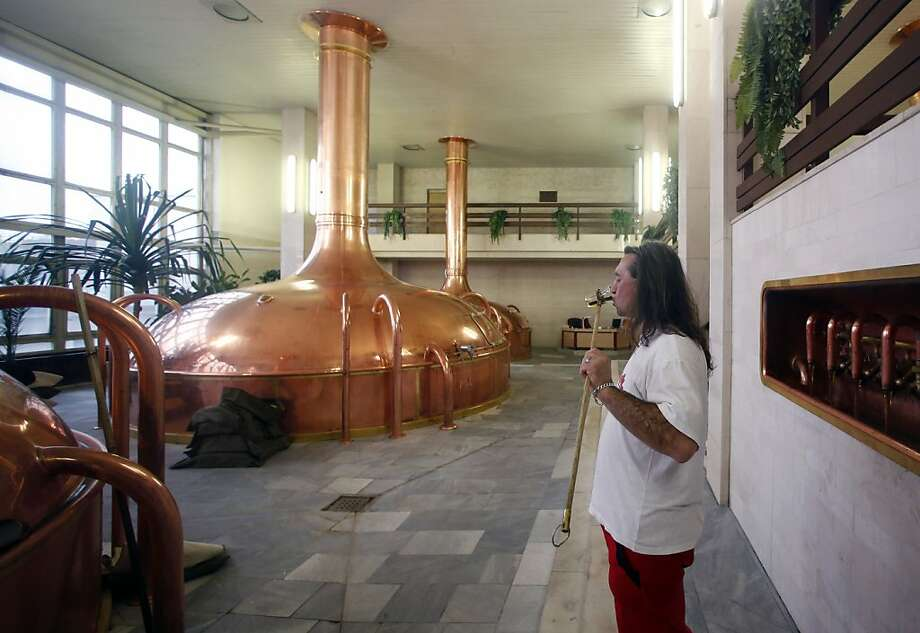 A brewer tastes the product at Budejovicky Budvar brewery in the Czech Republic. Budvar has a full-bodied taste not easily confused with its American rival's. Photo: Petr David Josek, Associated Press