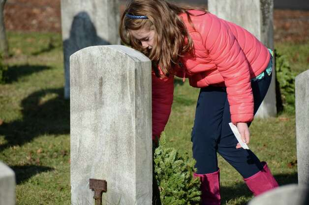 Katie Faye lays a wreath on a fallen soldier's headstone during the Wreaths Across America ceremony at Veterans Cemetery last Saturday, Dec. 15, 2012, in Darien, Conn. Photo: Jeanna Petersen Shepard