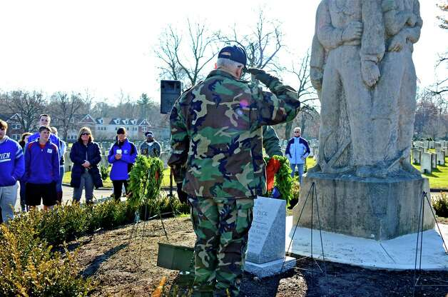 Veteran Pete Kenyon, who served in the Navy, lays a remembrance wreath, and then salutes in respect, in memory of those who served and are serving in the Unites States Navy, during the Wreaths Across America ceremony at the Veterans Cemetery in Darien on Saturday, Dec. 15, 2012. Photo: Jeanna Petersen Shepard