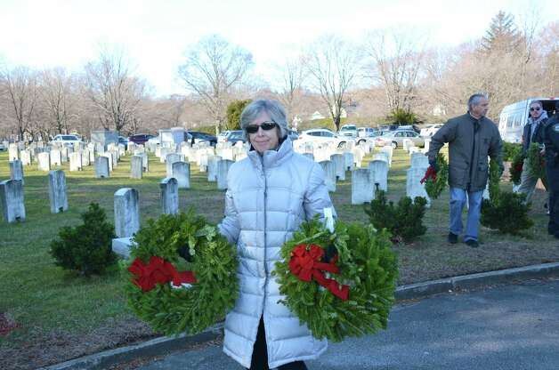 Becky Siciliano carrying two wreaths to place on the gravestones of two fallen soldiers, during the Wreaths Across America ceremony at Veterans Cemetery last Saturday, Dec. 15, in Darien, Conn. Photo: Jeanna Petersen Shepard