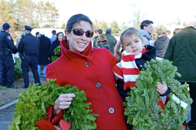 Mother and daughter, Tabitha and Tatum Wunderlich carry wreaths to place on soldiers' headstones during the Wreaths Across America ceremony at Veterans Cemetery last Saturday, Dec. 15, 2012, in Darien, Conn. Photo: Jeanna Petersen Shepard
