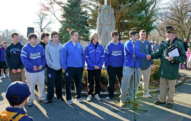 The Darien High School football team presents a check to VFW Phil Kraft, at the Wreaths Across America ceremony on Saturday, Dec. 15, 2012. Photo: Jeanna Petersen Shepard