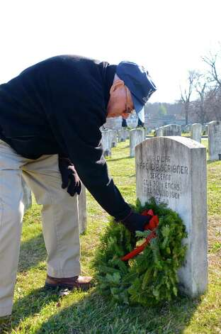 Charles Scribner lays a wreath on his father's grave, Sergeant Harold Scribner, during the Wreaths Across America ceremony at Veterans Cemetery last Saturday, Dec. 15, 2012. Darien, Conn. Photo: Jeanna Petersen Shepard