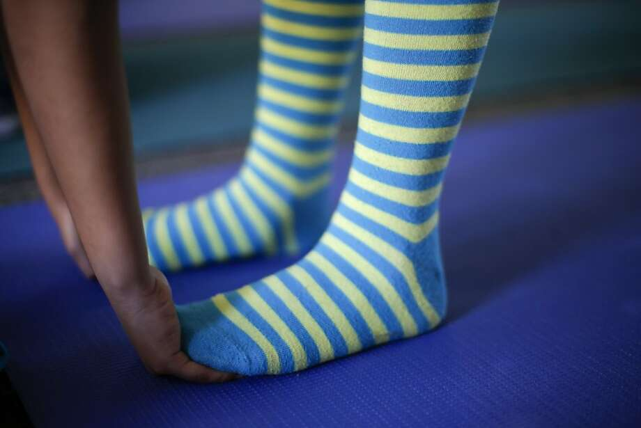 In this Dec. 11, 2012 picture, fourth grader Ashley Moreno reaches her toes during a yoga class at Capri Elementary School in Encinitas, Calif. Administrators of the Encinitas Union School District are treading softly as they pioneer what is believed to be the first district-wide yoga program of its kind, while trying to avoid a legal dispute over whether yoga is just exercise or an intrinsically spiritual practice. (AP Photo/Gregory Bull) Photo: Gregory Bull, Associated Press