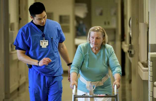 Physical therapist Howard Lin works with Silvana Bourg as she recovers from heart surgery at St. Luke's Episcopal Hospital on Wednesday, Nov. 7, 2012, in Houston. ( Brett Coomer / Houston Chronicle ) Photo: Brett Coomer, Houston Chronicle / © 2012 Houston Chronicle