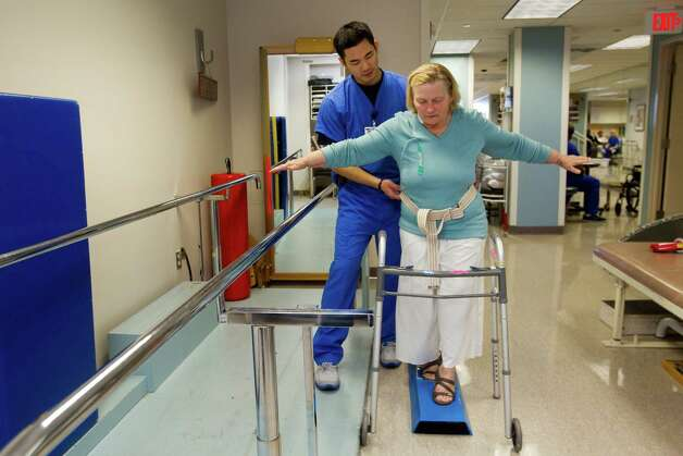 Physical therapist Howard Lin works with Silvana Bourg as she recovers from heart surgery at St. Luke's Episcopal Hospital. Photo: Brett Coomer, Houston Chronicle / © 2012 Houston Chronicle