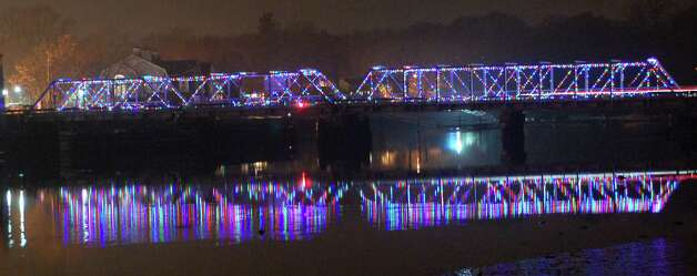 The Bridge Street bridge reflects the festive season as its holiday lights glow in the Saugatuck River. Photo: Jarret Liotta / Westport News contributed
