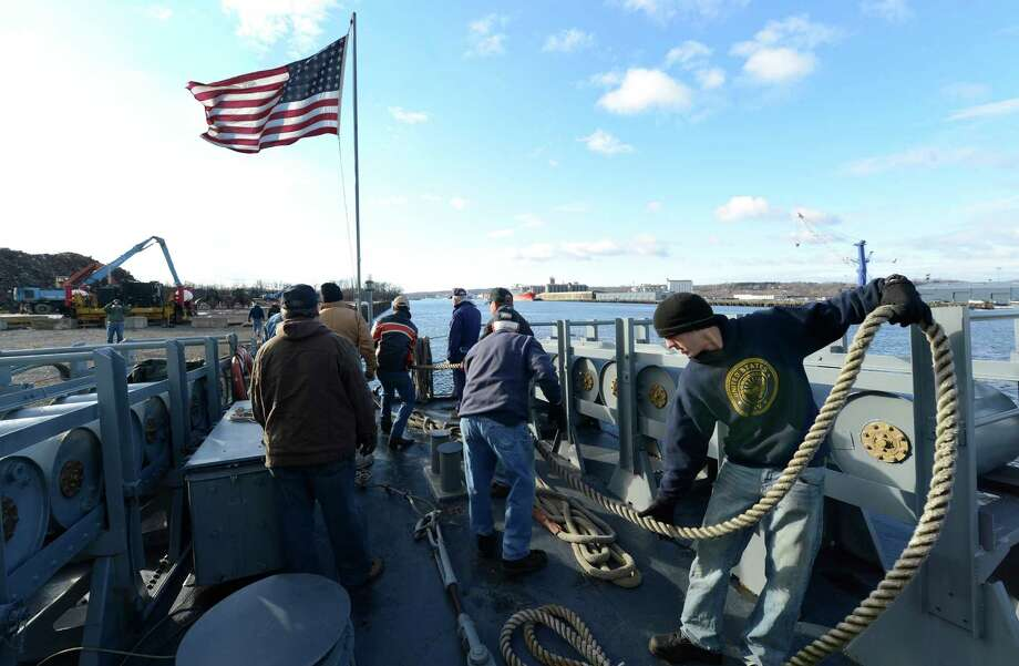 U. S. Navy Petty Officer 3rd. Micah Farrell, right, of the Milton Training Center in Wilton, pulls lines to make fast the USS Slater after it moved from the Albany, N.Y. side of the Hudson River to the Rensselaer side for its winter berth during its semi annual sail across the channel on Dec 19, 2012.   Farnsworth was one of the members of the regular Navy who volunteered to assist in the move of the ship.    (Skip Dickstein/Times Union) Photo: Skip Dickstein / 00020379A