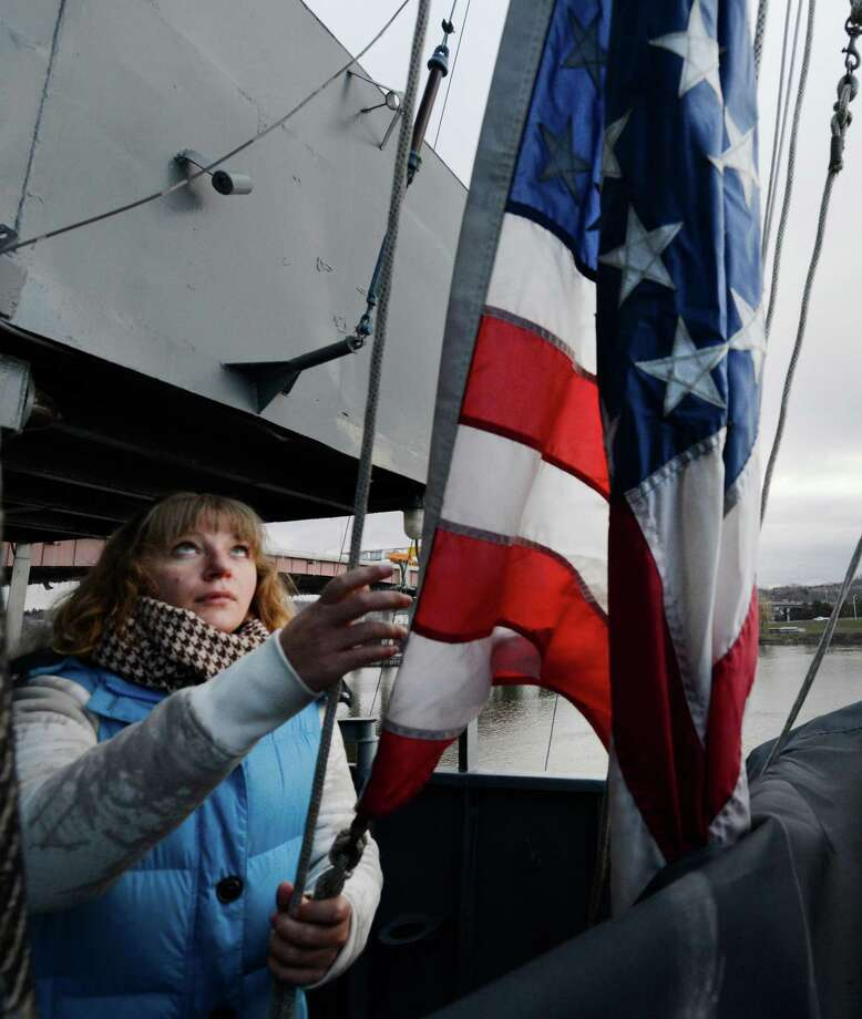 Heather Mason, interpretations coordinator, raises the American flag as the USS Slater  moves from the Albany, N.Y,. side of the Hudson River to the Rensselaer side for its winter berth Dec 19, 2012.     (Skip Dickstein/Times Union) Photo: Skip Dickstein / 00020379A