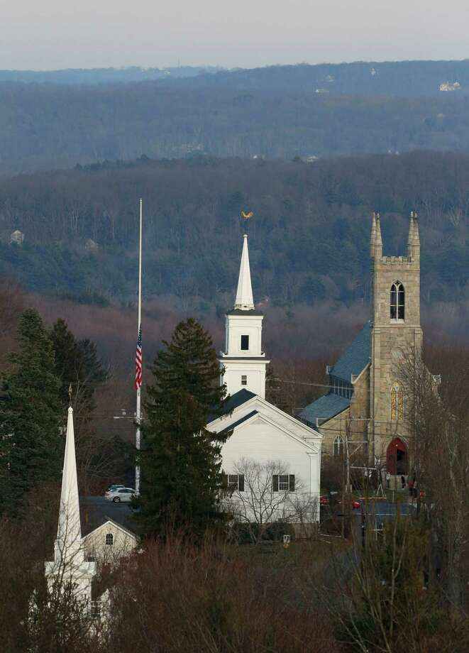 Church steeples viewed against the backdrop of rolling, wooded hills reflect the bucolic nature of Newtown, a quintessential small New England town. But even in this  landscape photographed Saturday, the flag at half staff signals that tragedy had shattered the peace. Photo: Julio Cortez, Associated Press / AP