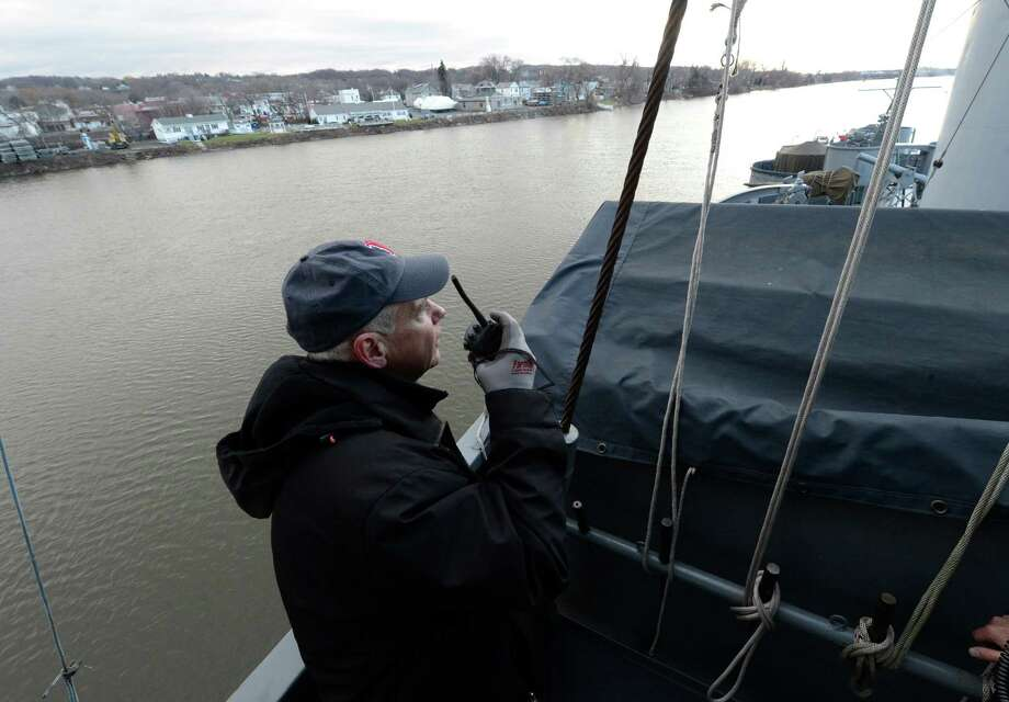 Harbor Pilot Paul Capel radios orders as the USS Slater is moved from the Albany, N.Y. side of the Hudson River to the Rensselaer side for its winter berth Dec 19, 2012.     (Skip Dickstein/Times Union) Photo: Skip Dickstein / 00020379A