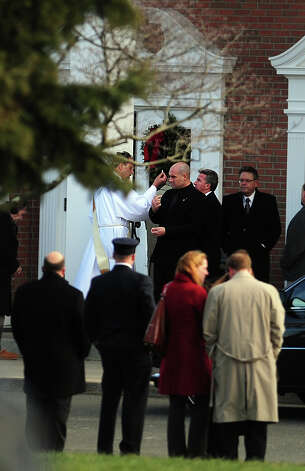 A priest offers communion outside St. Rose of Lima Roman Catholic Church in Newtown, Conn. during funeral services for Caroline Previdi, a student victim of the Newtown shootings, Wednesday, Dec. 19, 2012. Photo: Autumn Driscoll / Connecticut Post
