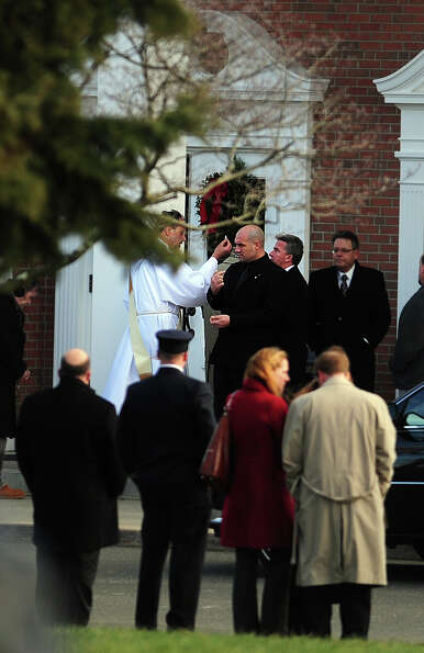 A priest offers communion outside St. Rose of Lima Roman Catholic Church in Newtown, Conn. during fu