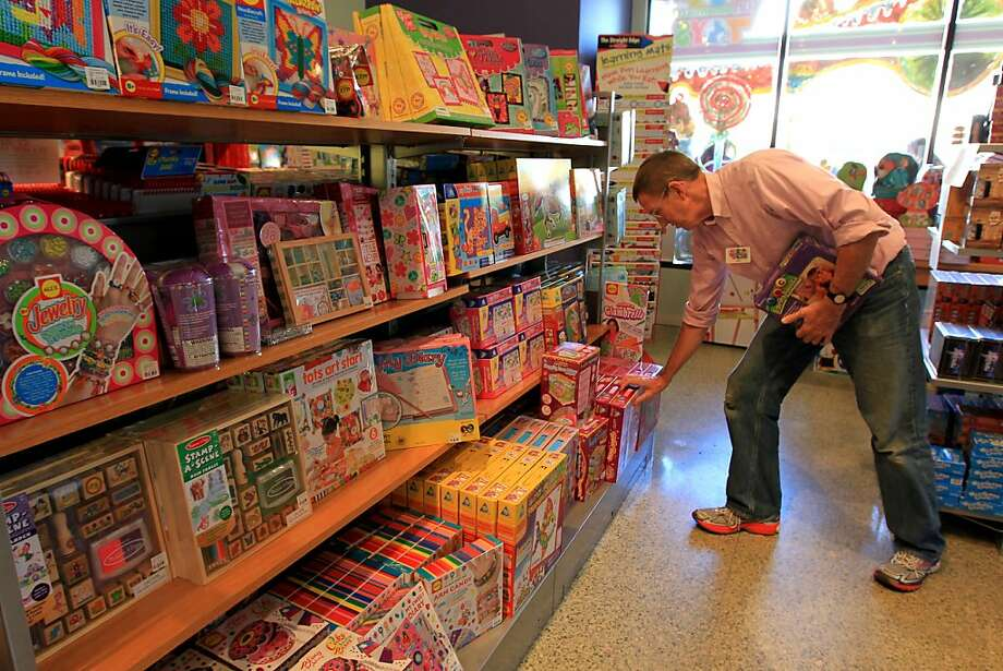 Stan Harbison stocks a shelf at Fundamentally Toys in Houston's Rice Village. Toymakers are upgrading their products with high-tech apps to appeal to children accustomed to playing with digital devices. Photo: Karen Warren, Houston Chronicle
