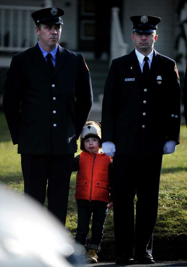 A child lines up with firefighters outside the funeral for Daniel Gerard Barden, a student victim of the Newtown shootings, Wednesday, Dec. 19, 2012 at St. Rose of Lima Roman Catholic Church in Newtown, Conn. Photo: Autumn Driscoll / Connecticut Post