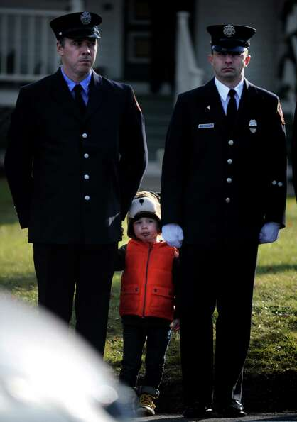 A child lines up with firefighters outside the funeral for Daniel Gerard Barden, a student victim of