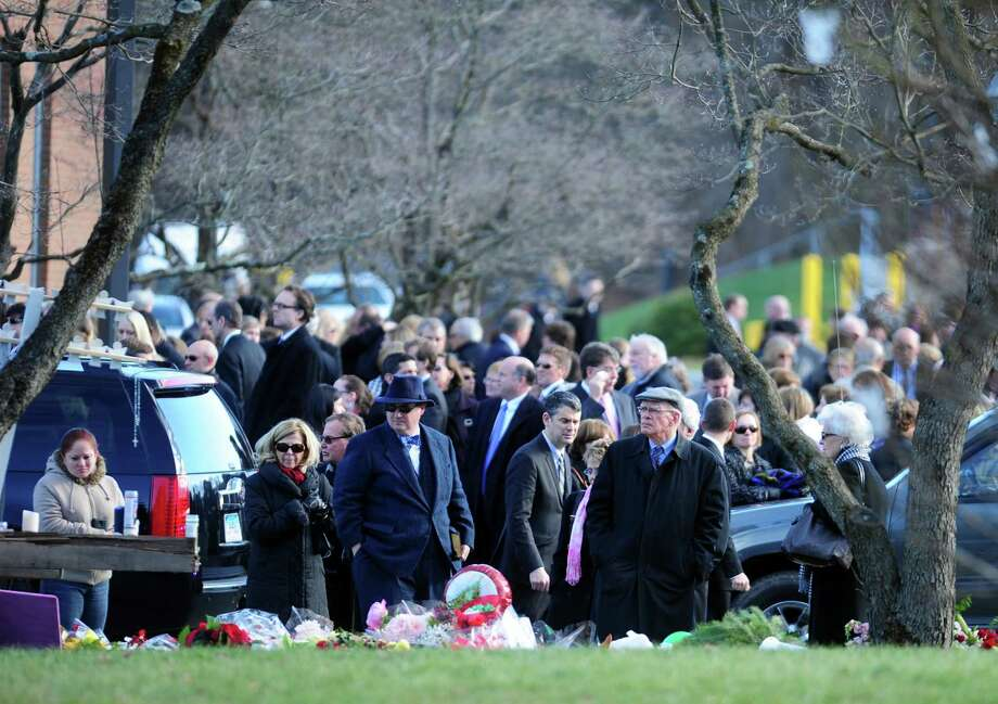 Mourners leave St. Rose of Lima Roman Catholic Church in Newtown, Conn. Wednesday, Dec. 19, 2012 following funeral services for Caroline Previdi, one of 20 children killed in a mass shooting at Sandy Hook Elementary School last week. Photo: Autumn Driscoll / Connecticut Post
