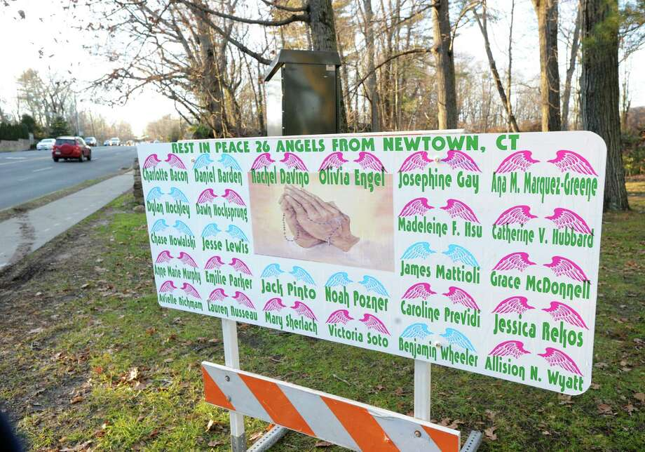 """Rest in Peace 26 Angels from Newtown, CT,"" reads a sign with the names of the victims of the Sandy Hook Elementary School shooting, on the northwestern corner of East Putnam Avenue and Hillside Road in Greenwich, Wednesday afternoon, Dec. 19, 2012. Photo: Bob Luckey / Greenwich Time"