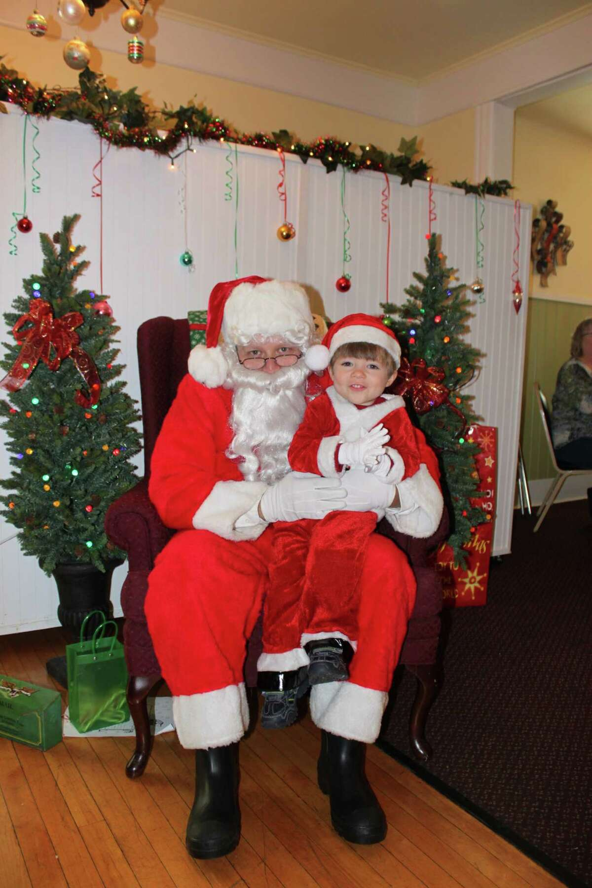 Hudson Treacy ? son of Dave and Nicole Treacy ? poses with Santa in his own mini Santa suit at the Girl Scout Breakfast with Santa event at Shawn P's at the Van Schaick Island Country Club in Cohoes.