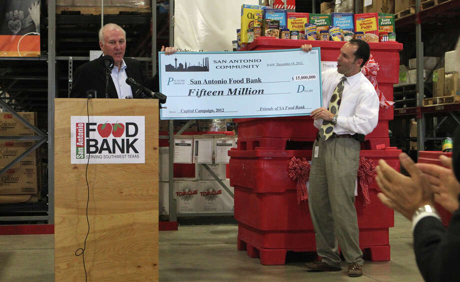San Antonio Spurs coach Gregg Popovich (left) and Eric Cooper (right), President and CEO of the San Antonio Food Bank, hold a symbolic check Wednesday December 19, 2012 at an event announcing that a number of different donations totaling $15 million has been made to the San Antonio Food Bank. The money will be used in many ways including to help with the San Antonio Food Bank's facility expansion project. Photo: JOHN DAVENPORT, San Antonio Express-News / ©San Antonio Express-News/Photo Can Be Sold to the Public