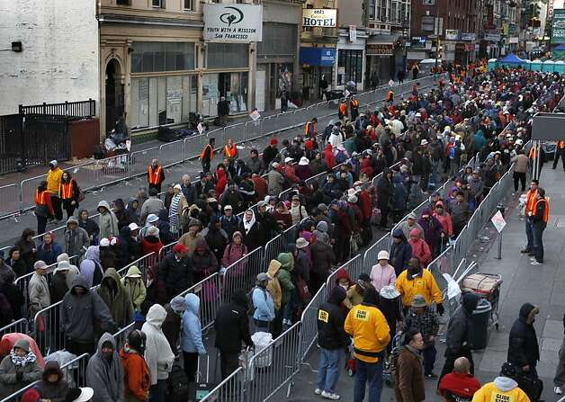 A long line of people zig-zags down Ellis Street for the annual grocery giveaway for those in need at Glide Memorial Church in San Francisco, Calif. on Wednesday, Dec. 19, 2012. Volunteers assembled and distributed 5,500 grocery bags this year. Photo: Paul Chinn, The Chronicle