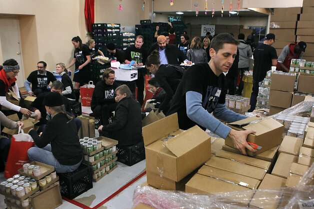 Ben Mahling opens cartons of canned food as other volunteers fill bags at the annual grocery giveaway at Glide Memorial Church in San Francisco, Calif. on Wednesday, Dec. 19, 2012. Volunteers assembled and distributed 5,500 grocery bags this year. Photo: Paul Chinn, The Chronicle