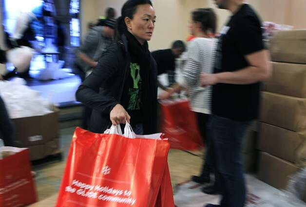 Mary Cha-Caswell rushes bags to other volunteers to fill at the annual grocery giveaway at Glide Memorial Church in San Francisco, Calif. on Wednesday, Dec. 19, 2012. Volunteers assembled and distributed 5,500 grocery bags this year. Photo: Paul Chinn, The Chronicle