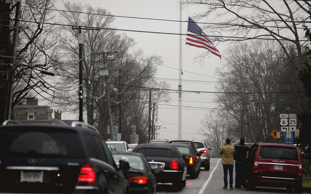A funeral procession follows the hearse carrying the casket of Sandy Hook Elementary School shooting victim, Jack Pinto, 6, Monday, Dec. 17, 2012, in Newtown, Conn. Pinto was killed when a gunman walked into Sandy Hook Elementary School in Newtown Friday and opened fire, killing 26 people, including 20 children. (AP Photo/David Goldman)