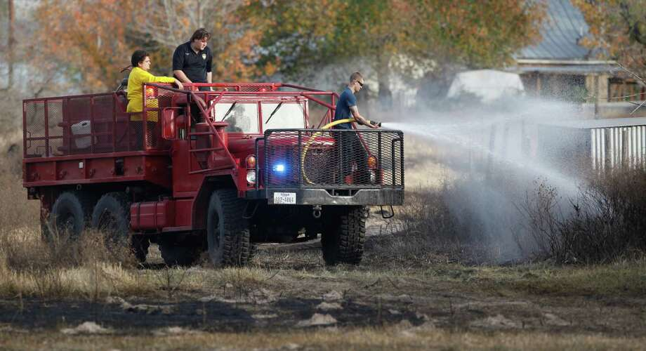 Firefighters work Wednesday afternoon Dec. 19, 2012 at the scene of a small grass and brush fire near the East Central School District campuses in southeast Beaxr County. Photo: William Luther, San Antonio Express-News / © 2012 San Antonio Express-News