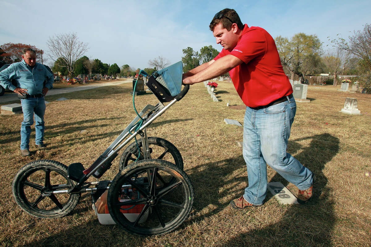 Tim Miller, Director of Texas EquuSearch, watches as the graves of two children, Roxanne Lynn Rudasill and Odis Wayne Rudasill are located in the Lytle Community Cemetery using a ground penetrating radar system employed by Glenn Zebrowski on December 19, 2012.