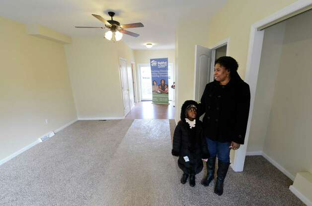 "Owner of 43 Alexander Street Luverne Patterson stands in the living room of her new home with her daughter Esther Patterson 5 on ""Morton's Walk"", a production of the Habitat for Humanity, Capital District which was dedicated in Albany, N.Y. Dec. 19, 2012.   (Skip Dickstein/Times Union) Photo: Skip Dickstein"