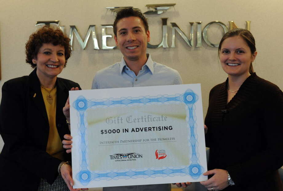 Eric Guzman, marketing coordinator at Interfaith Partnership for the Homeless, accepts a check for $5,000 of in-kind advertising from Charmaine Ushkow (left), community relations manager at the Times Union, and Jennifer Patterson, News and Information Services coordinator, on Tuesday, Dec. 18, 2012 at the Times Union in Colonie, NY. (Michael P. Farrell/Times Union)