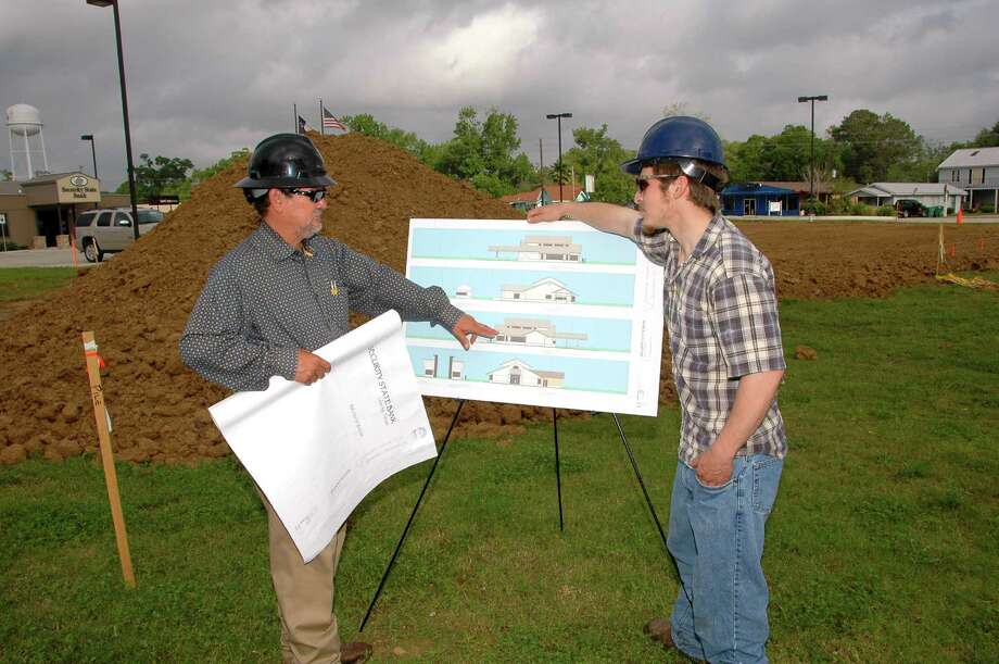 Larry Kness, left, owner of Nest Construction Service and a San Jacinto College graduate, reviews construction-site plans with his son Justin, who serves as an assistant construction superintendent.